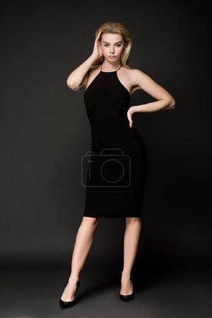 Photo pour Attrayant élégant fille en robe noire posant sur noir - image libre de droit