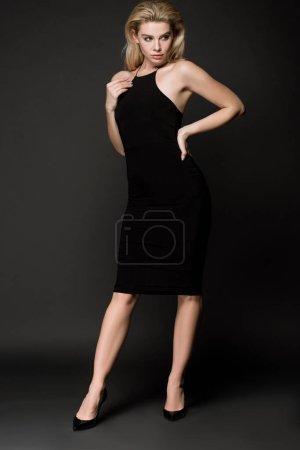 Photo pour Jolie fille blonde en robe noire élégante, posant sur fond noir - image libre de droit