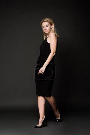 Photo pour Belle jeune femme en robe noire élégante, posant sur fond noir - image libre de droit