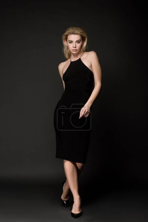 Photo for Attractive elegant girl in black dress posing on black - Royalty Free Image