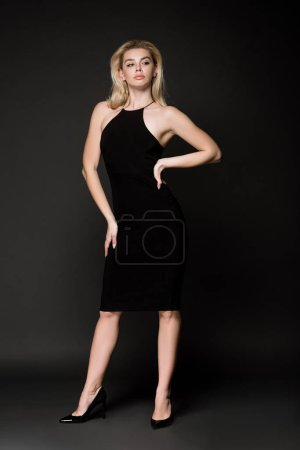 Photo pour Modèle blonde séduisante dans une robe noire posant sur fond noir - image libre de droit