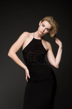 Photo for Attractive elegant girl in black dress posing isolated on black - Royalty Free Image
