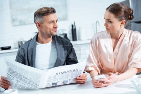 Photo for Man in robe reading business newspaper while woman using smartphone during breakfast in kitchen - Royalty Free Image