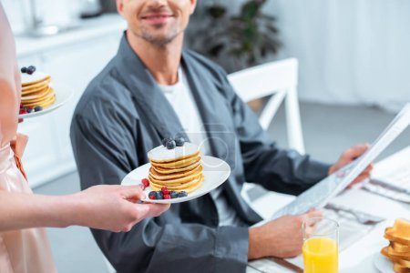 Photo for Cropped view of woman holding plates with pancakes while man reading newspaper during breakfast in kitchen - Royalty Free Image