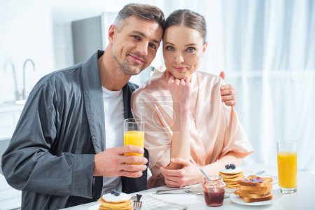 Photo for Handsome man holding orange juice and hugging woman during breakfast in morning - Royalty Free Image
