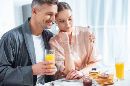 Photo for Handsome man holding orange juice and hugging smiling woman during breakfast in morning - Royalty Free Image