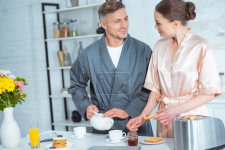 Photo for Handsome man pouring tea while woman preparing toasts with jam during breakfast - Royalty Free Image