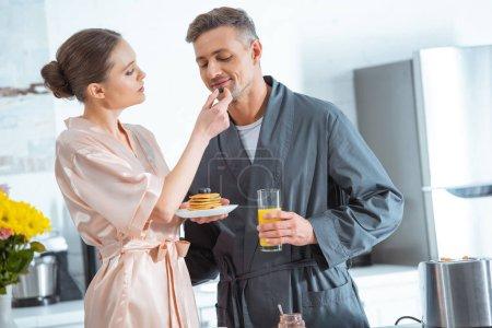 Photo pour Beau couple en peignoirs avec jus d'orange et crêpes pendant le petit déjeuner en cuisine - image libre de droit