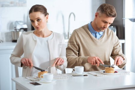 Photo for Selective focus of adult couple sitting at table and ignoring each other during breakfast in morning - Royalty Free Image
