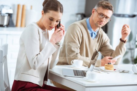 Photo for Man looking at woman secretly talking on smartphone during breakfast - Royalty Free Image
