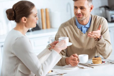 Photo for Beautiful couple looking at each other and talking during breakfast in morning - Royalty Free Image