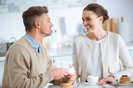Photo for Beautiful smiling couple looking at each other during breakfast in morning - Royalty Free Image