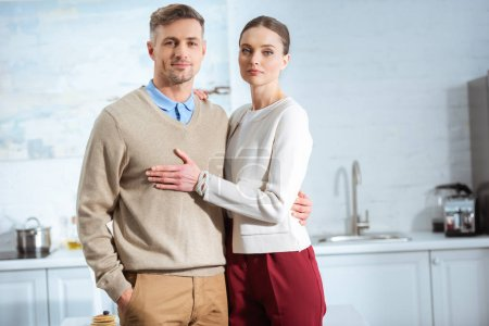 adult couple in casual clothes looking at camera and embracing in kitchen