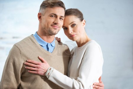 beautiful adult couple in casual clothes looking at camera at home