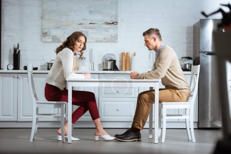 Photo for Dissatisfied couple sitting with clenched fists at table in kitchen - Royalty Free Image