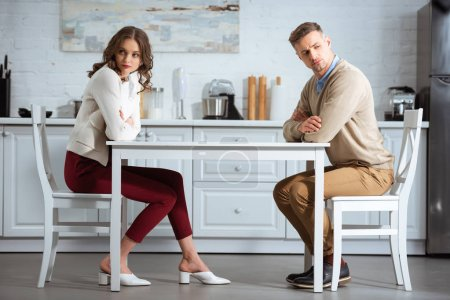 Photo for Dissatisfied couple sitting with arms crossed at table in kitchen - Royalty Free Image