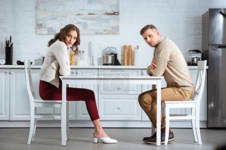 Photo pour Dissatisfied couple sitting with arms crossed at table in kitchen - image libre de droit