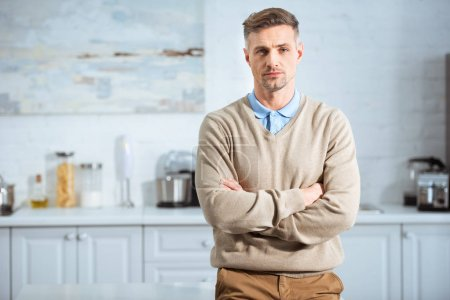 Photo for Handsome man in casual clothes with arms crossed looking at camera in kitchen - Royalty Free Image