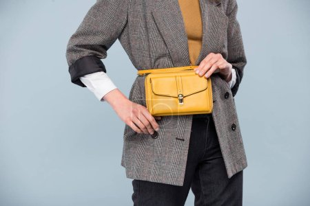 Photo for Cropped view of stylish woman in formal wear holding bag and posing isolated on grey - Royalty Free Image