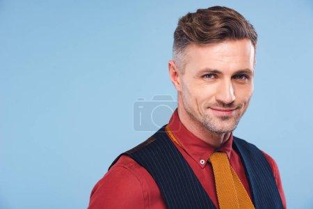Photo pour Portrait de bel homme élégant et souriant en tenue formelle isolé sur bleu - image libre de droit