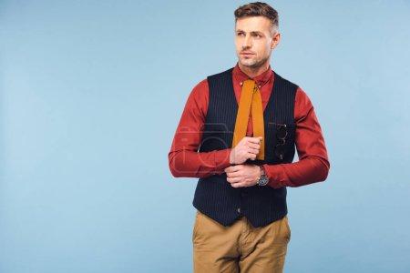 Foto de Hombre guapo elegante en ropa formal ajuste camisa y mirando lejos azul aislado en - Imagen libre de derechos