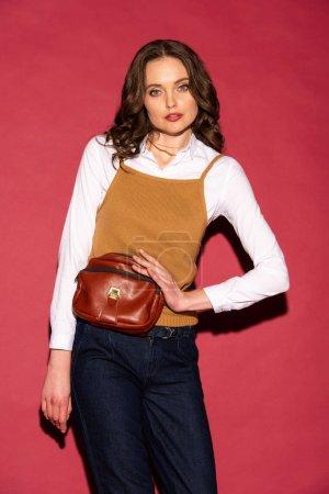 Photo pour Belle femme en vêtements tenant sac en cuir, en regardant la caméra et en posant sur fond rouge - image libre de droit