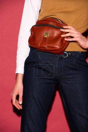 Photo pour Vue partielle de la femme tenant le sac en cuir sur fond rouge - image libre de droit