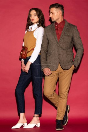 Photo for Attractive trendy couple in formal wear posing on red background - Royalty Free Image