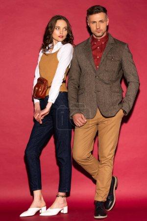 Photo pour Attrayant couple à la mode dans l'usure formelle posant sur fond rouge - image libre de droit