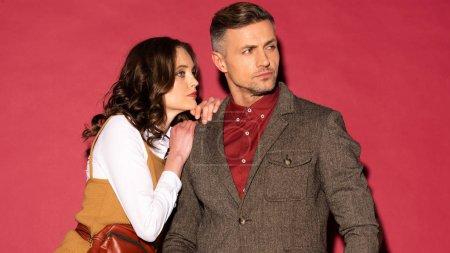 Foto de Atractiva pareja moda en formal desgaste posando y mirando lejos sobre fondo rojo - Imagen libre de derechos