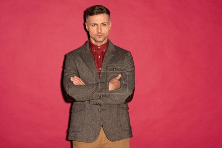 Photo for Handsome stylish man in formal wear with arms crossed looking at camera on red background - Royalty Free Image