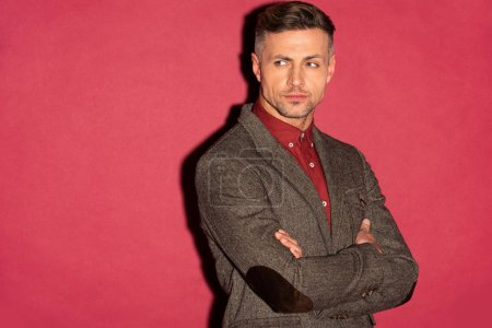 Photo for Handsome stylish man in formal wear with arms crossed looking away on red background - Royalty Free Image