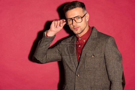 Photo for Stylish man in formal wear looking at camera and adjusting glasses on red background - Royalty Free Image