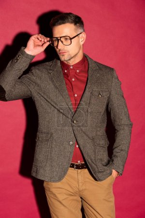 confident stylish man in formal wear and glasses looking away on red background