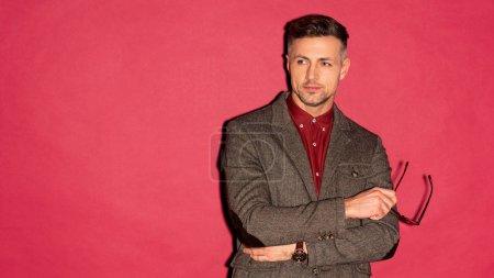 Foto de Hombre guapo elegante en ropa formal con los brazos cruzados sobre fondo rojo con espacio de copia - Imagen libre de derechos