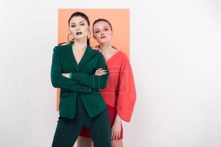 Photo pour Confiant à la mode jeunes femmes regardant la caméra et posant avec corail sur fond de vie - image libre de droit