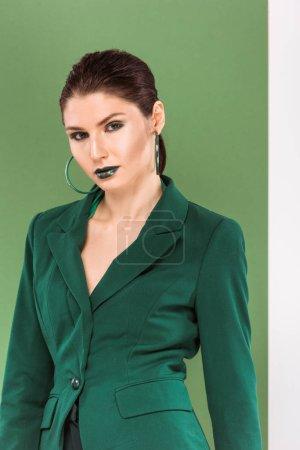 Foto de Hermosa mujer moda en ropa formal mirando a cámara y posar con verde sobre fondo - Imagen libre de derechos