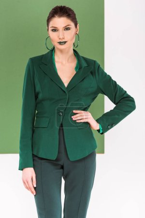 Photo for Beautiful fashionable woman with hand on hip in formal wear posing with sea green on background - Royalty Free Image