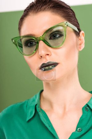Foto de Retrato de hermosa mujer moda en gafas de sol con verde sobre fondo - Imagen libre de derechos