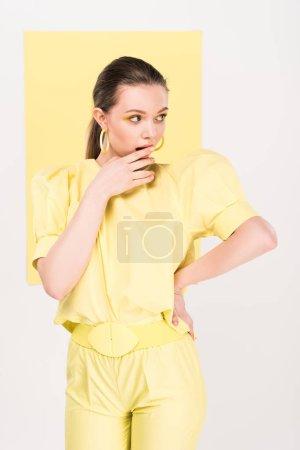 Photo pour Belle fille élégante toucher le menton et posant avec la lumière sur le fond - image libre de droit