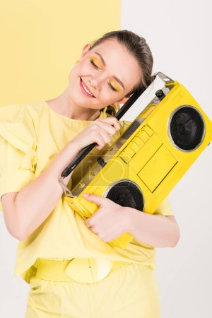 Photo for Stylish girl holding retro boombox and posing with limelight on background - Royalty Free Image