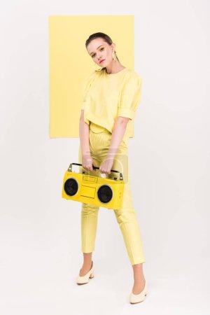 Photo pour Fille élégante tenant boombox rétro et posant avec la lumière sur le fond - image libre de droit