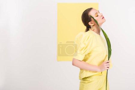 Photo pour Belle fille élégante tenant feuille et posant avec les feux de la rampe sur fond - image libre de droit
