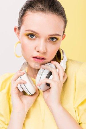 Photo pour Belle fille élégante tenant écouteurs et regardant la caméra avec la lumière sur le fond - image libre de droit