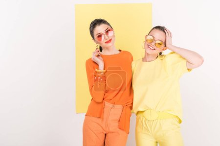 Photo for Beautiful fashionable girls in sunglasses posing with limelight on background - Royalty Free Image