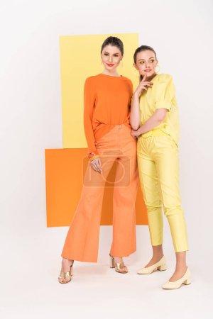 Photo pour Belles jeunes femmes élégantes posant avec curcuma et la lumière sur le fond - image libre de droit