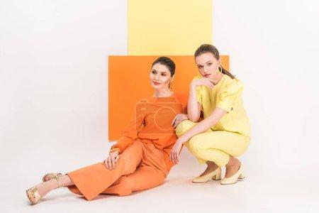 Photo pour Belles filles élégantes assis et posant avec curcuma et la lumière sur le fond - image libre de droit