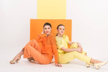 Photo for Beautiful stylish girls sitting, looking at camera and posing with turmeric and limelight on background - Royalty Free Image