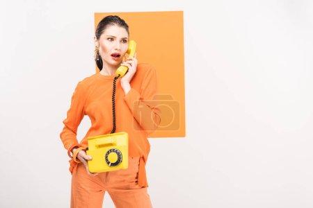 Photo pour Belle femme à la mode rétro téléphone et posant avec curcuma sur fond - image libre de droit