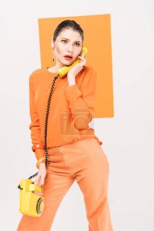 Foto de Sorpresa de moda joven hablando por teléfono retro y posando con cúrcuma sobre fondo - Imagen libre de derechos